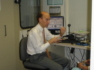 audiologist sitting at table with technical equipment